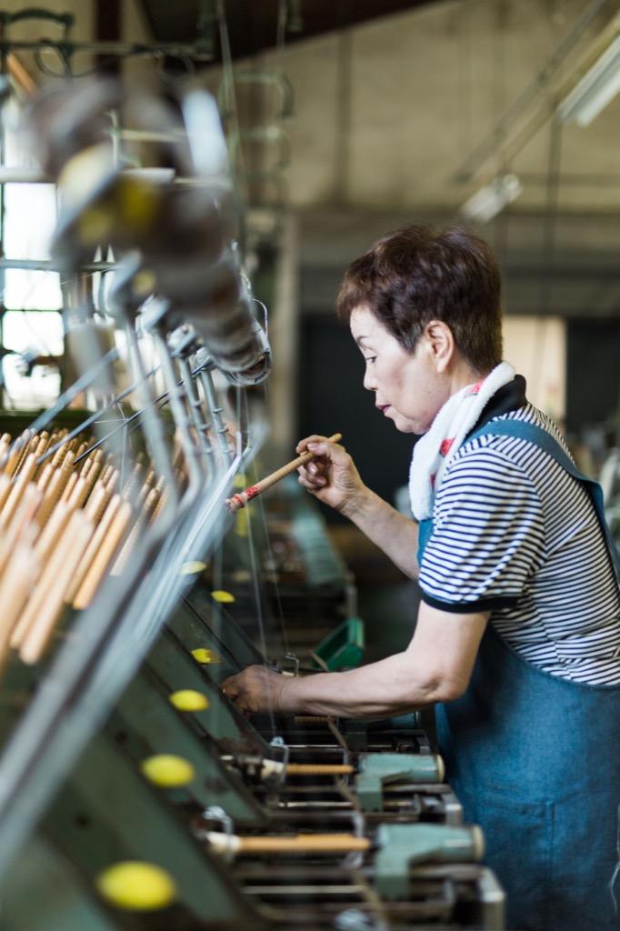 織布工場で管巻の機械のオペレーションをする様子
